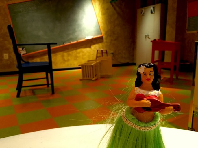 In-game: A little hula girl statue sits in the foreground with a twisted and askew classroom in the background.