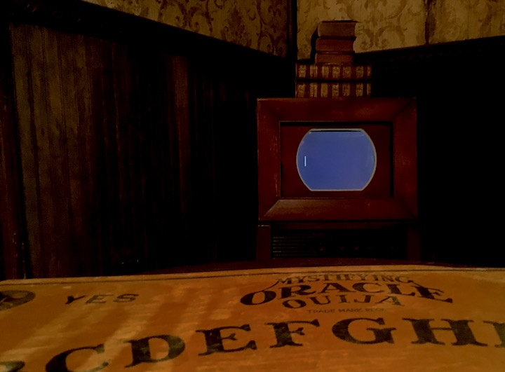 In-game: A Ouija board in the foreground, a aged hotel with an old television in the background.