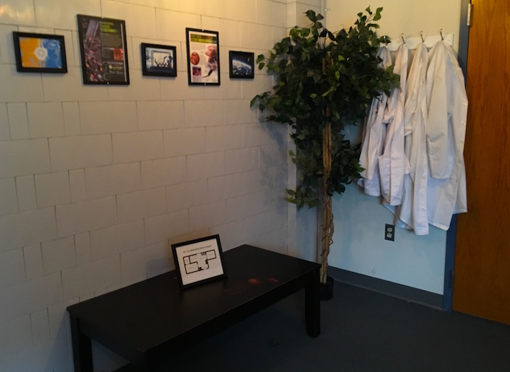 In-game: A bland room with a plant a coffee table, and a few lab coats hanging on the wall.