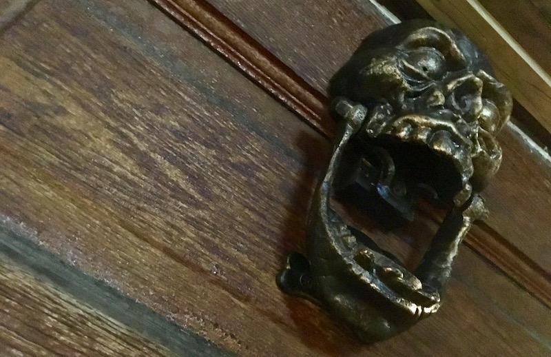 In game: a large brass skull door knocker.