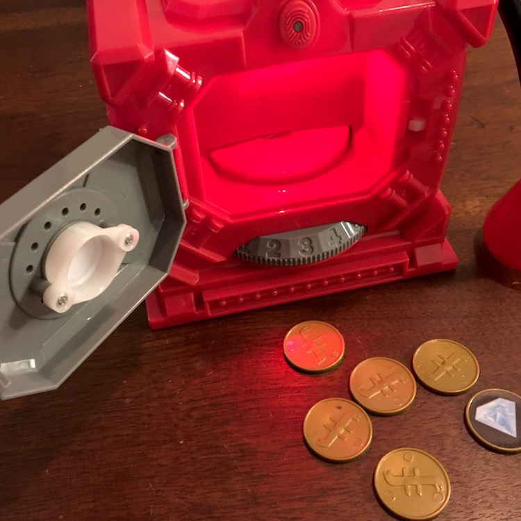 The safe popped open, a few coins are laying at its base.