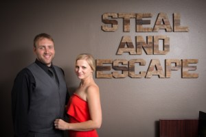 The founders of Steal And Escape in front of their logo; they are a very pretty couple.
