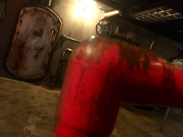In-game: A dramatically lit, metal bunker with a red pipe in the foreground.