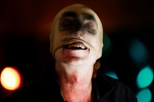 Image of the game's killer with a dirty stocking over his head, mouth exposed, and blood staining his neck.