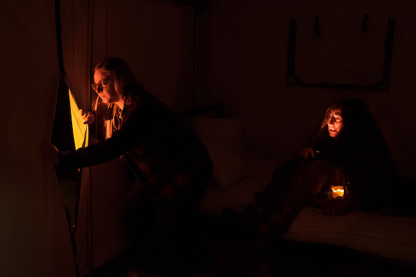 In-game: Two women in a dark candle-lit tent nervously peering out of the flap.