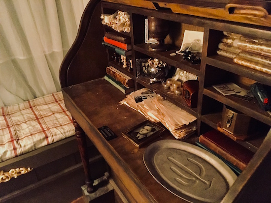 In-game: an antique rolltop desk filled with books and trinkets next to a small bed.