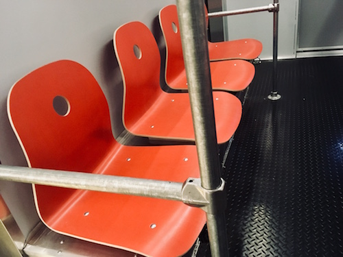 In-game: Orange seating a metal polls in the interior of the subway car.