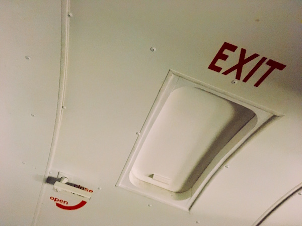 In-game: A rounded cabin door marked EXIT, with an open and close lever latch.
