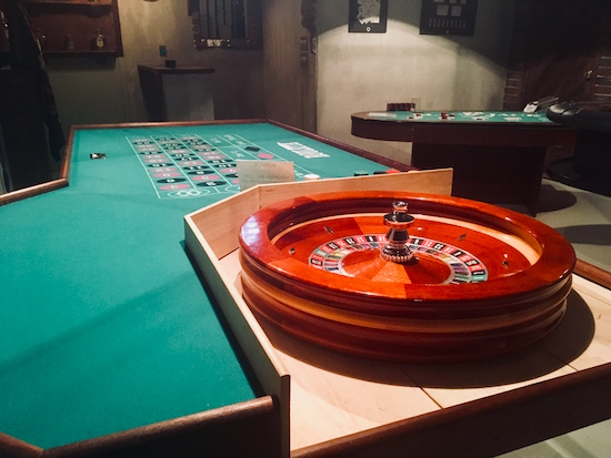 In-game: A roulette table in the foreground, a card table in the background.