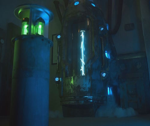 In-game: A sci-fi science lab with tubes filled with glowing green material, and a large metal and glass chamber with lighting running through it.
