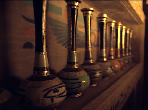 In-game: A series of colored bottles on a ledge within an Egyptian tomb.