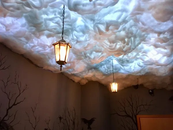 A ceiling of cotton clouds with old lanterns hanging from it. The clouds are illuminated like lightning.
