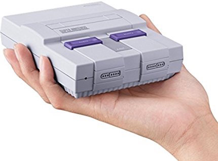A hand holding the tiny Super Nintendo Classic in the palm of a hand.