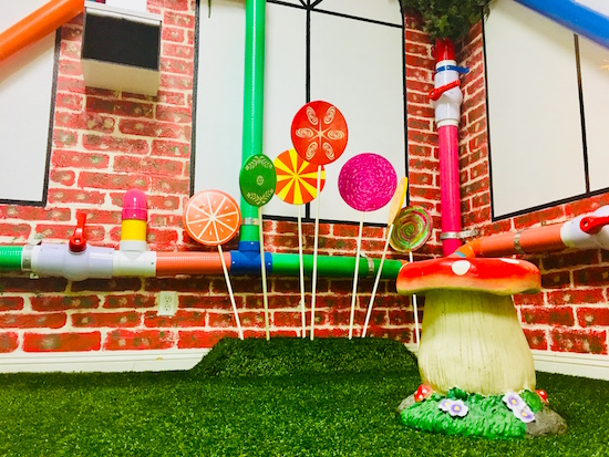 In-game: A Wonka-esque factory with green grass, brick walls, and lollypops growing from the ground.