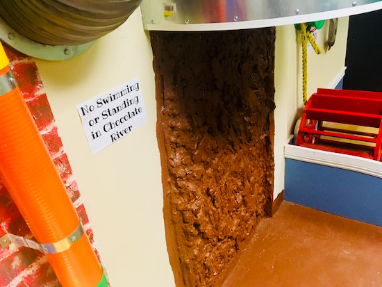 In-game: A wall of fudge made to look like a chocolate waterfall flowing into a river of chocolate.