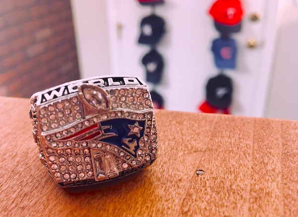 In-game: a Patriots World Champion, diamond encrusted ring sitting on a table, a door covered in sports caps blurred in the background.