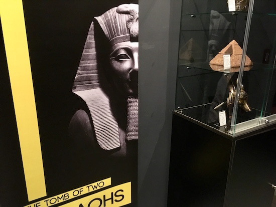 In-game: Another display case with a small pyramid and an Anubis bust.