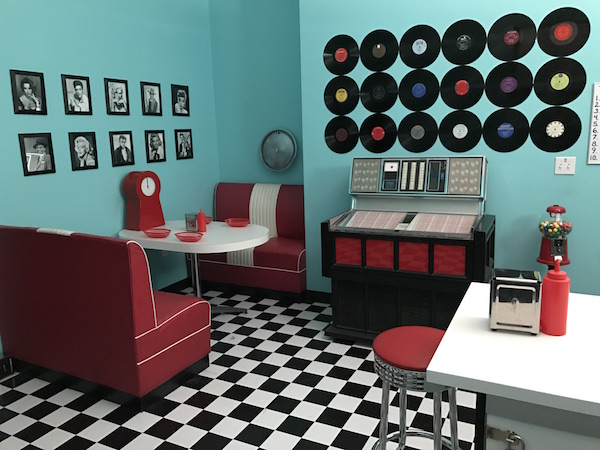 In-game: A 1950's diner with red and white furniture an old jukebox, and records on a sky blue wall.