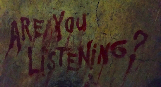 "Close up of the wall, ""Are you listening?"" is painted in blood."