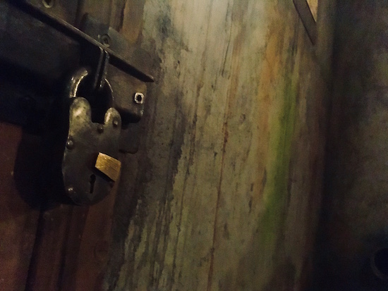 In-game: A closeup of a large old lever padlock against a gross and worn wall.
