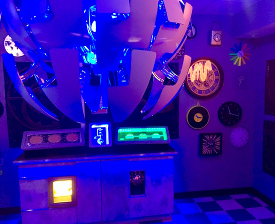 In-game: An elaborate ceiling hanging light, a wall of assorted clocks, and an illuminated control console.