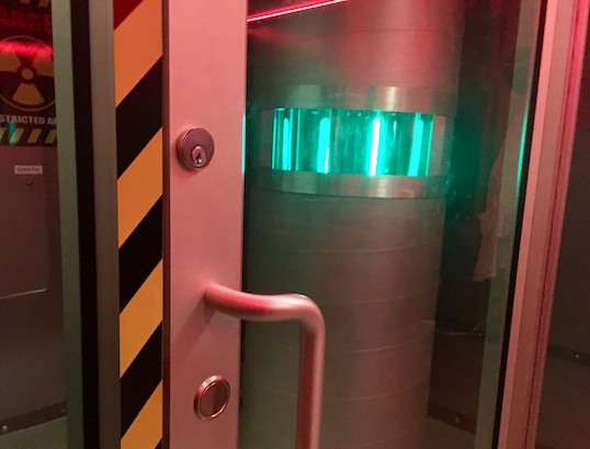 In game: A glass door with a green glowing reactor behind it.