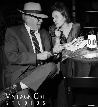 Lisa's father in a fedora and suite sitting at a small table looking at puzzles with Lisa.