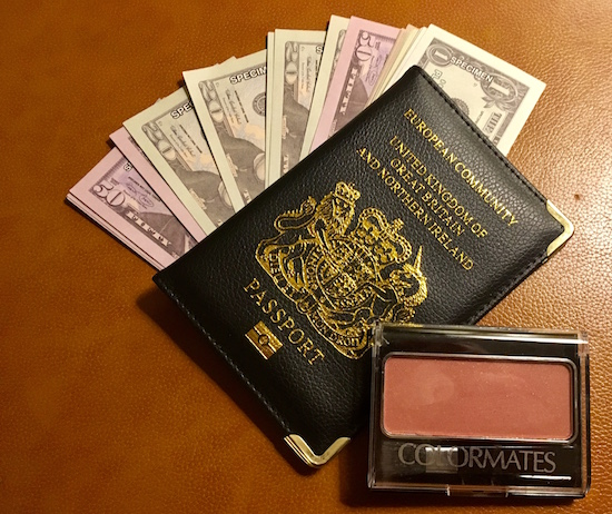 Play money fanned out, a passport, and makeup.