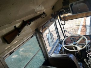In-game: Overhead of the driver's seat. There is a rifle mounted to the wall, and a lot of extra wiring.