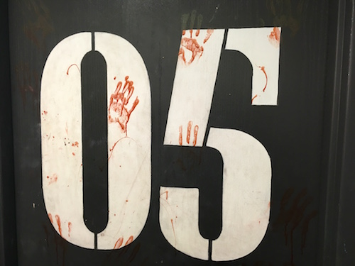 In-game: the number 05 painted to the wall and covered in bloody handprints.