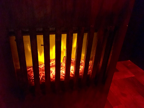 In-game: a burning furnace in a dark room.
