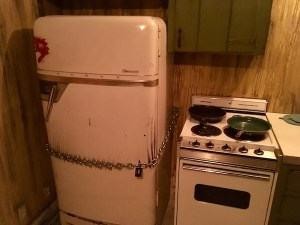 In-game: a rundown kitchen with an old stove and refrigerator locked shut with a chain and padlock.