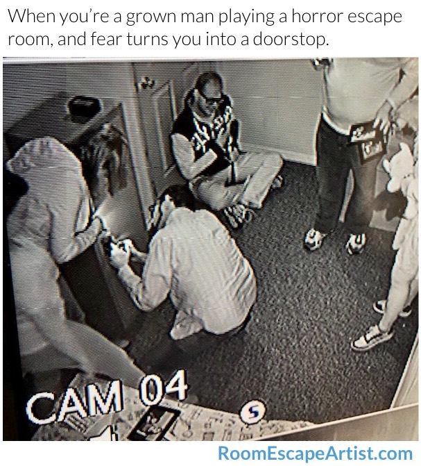 Escape room camera image of a team puzzling and a guy cowering and sitting against a door, blocking it.