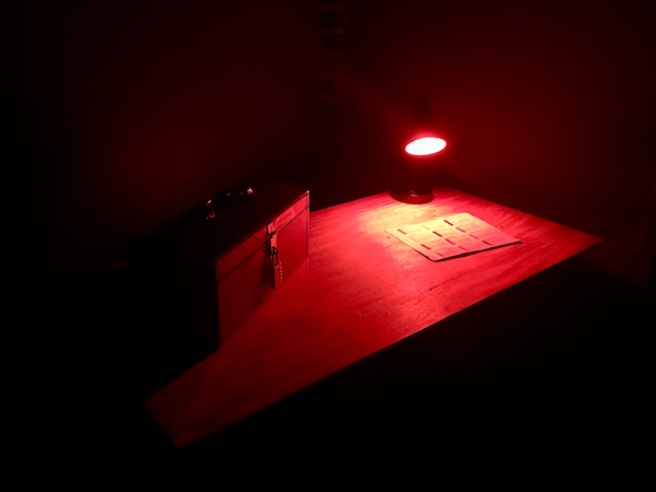 In-game: a dark room with a table lit red and a locked toolbox on top of it.