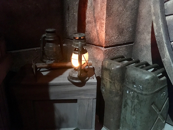 In-game: A close up of a lantern, water tanks, and a crate in front of an archeological dig site.