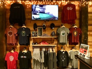The Escape Game Nashville's merchandise area with a variety of t-shirts, hoodies, hats, and other products.