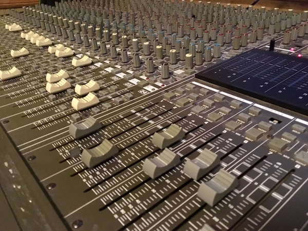 In-game: closeup of a large mixing board.