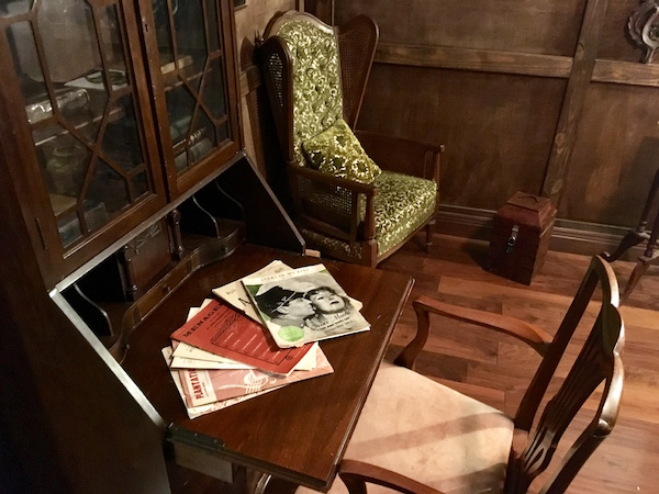 In-game: An old secretary's desk open beside a large comfortable chair in a wood floor and walled room.