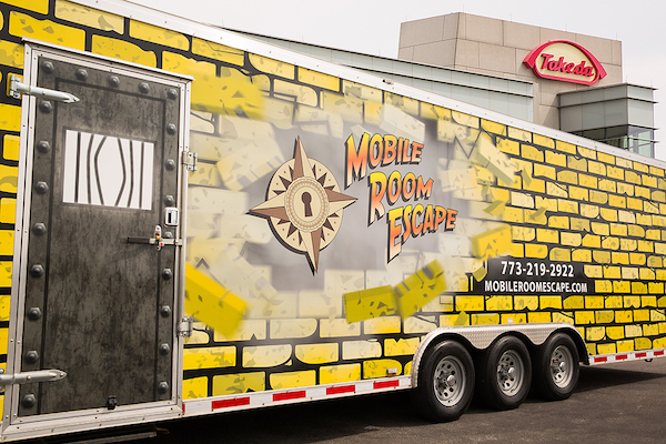 Mobile Room Escape Chicago trailer exterior, a yellow bricked wall with a steel door and their compass rose logo.
