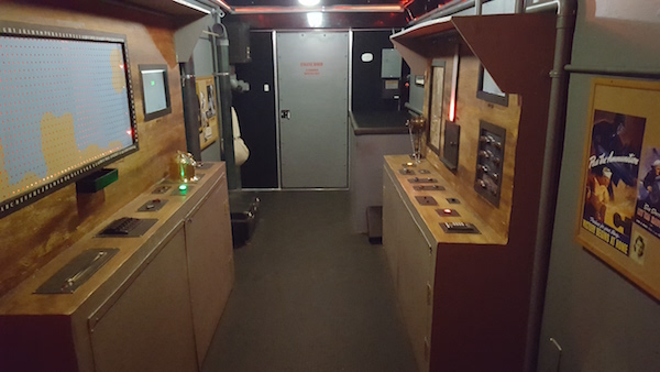 Mobile Room Escape Chicago interior - a submarine lined with puzzle stations. WWII propaganda posters hang on the wall.