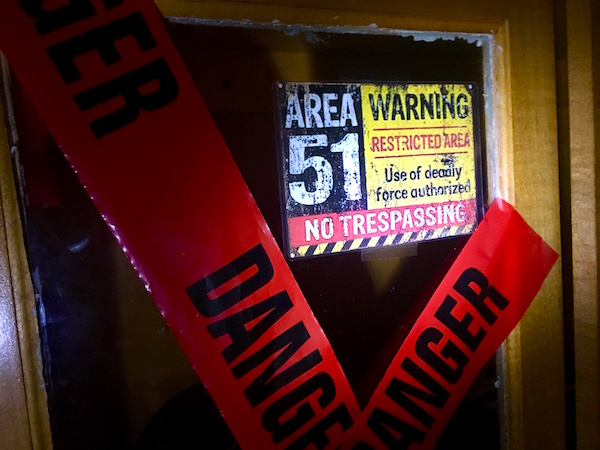 "In-game: a cabinet marked with red danger tape and labeled, ""Area 51 Restricted Area."""