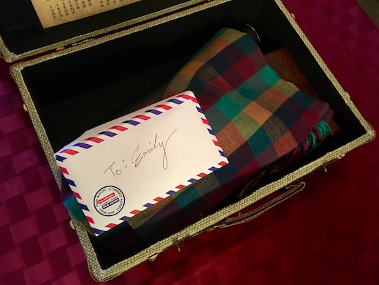 One suitcase open, a scarf and a letter addressed to Emily are visible.
