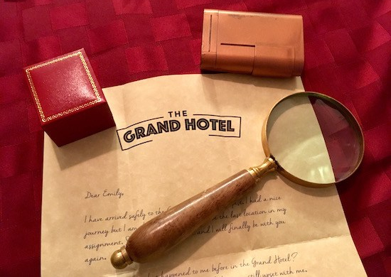 A letter to Emily written on Grand Hotel stationary, a ring box, a magnifying glass, and a small copper lockbox.