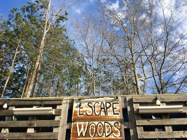 The rusty hand painted Escape Woods sign.