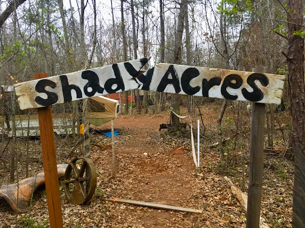 "The entry way to The Shiners. A broken archway reads, ""Shady Acres."" Beyond is a wooded trailer park."