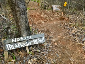 """In-game: A hand painted wooden sign leans against a tree. It reads, """"Notis! Trespasser get shot."""""""