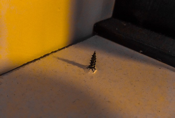A screw protruding from a piece of wood.
