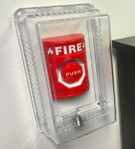 In-game: A fire alarm push button locked behind a clear plastic casing.