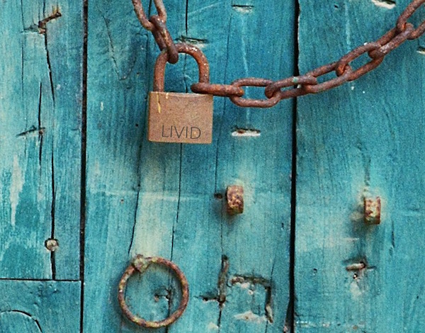 A blue door locked by an old golden padlock labeled LIVID.