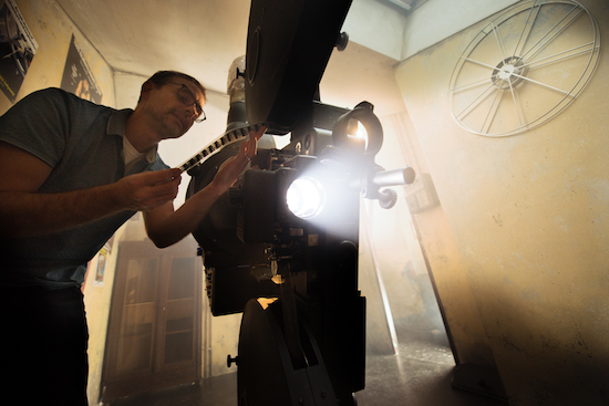 In-game: Promo images of a man operating an old film projector.